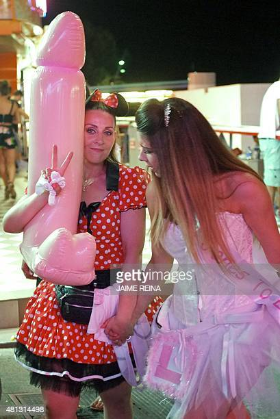 Two girls pose with an inflatable penis in Punta Ballena street in Magaluf holiday resort in Calvia on the Spanish Mallorca Island on July 19 2014...