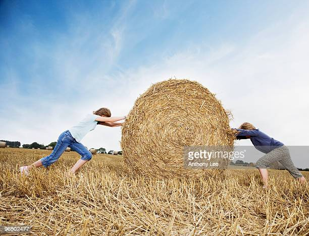 Two girls pushing against bale of hay