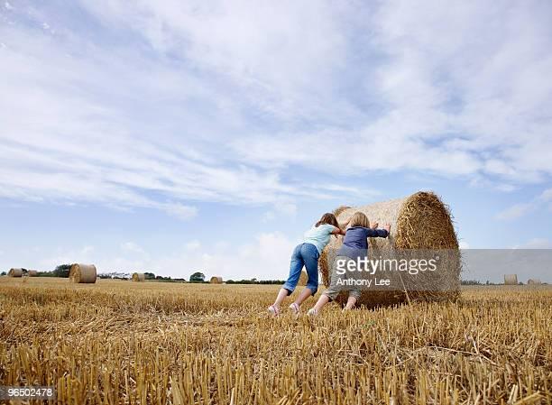 Two girls pushing bale of hay