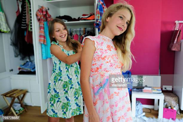 Two girls putting on dresses