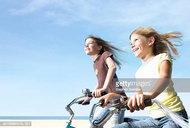 Two girls (8-10) riding bicycles on beach