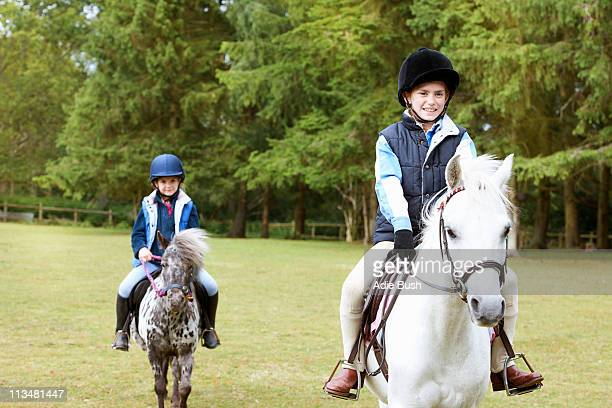 Two girls riding their ponies