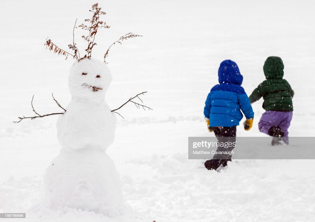 Two girls run through past their snowman on December 27, 2012 in Greenfield, Massachusetts. A serious winter storm that caused tornados in the South on Christmas Day swept across the Northeast on Thursday, bringing snow, sleet, rain and causing dangerous travel conditions.