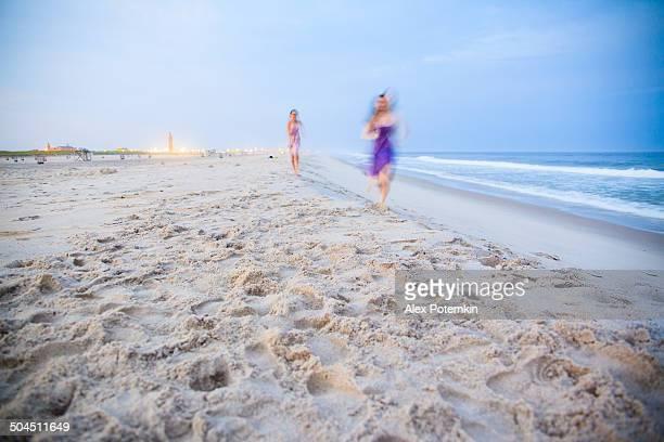Two girls running at the Jones Beach at the sunset