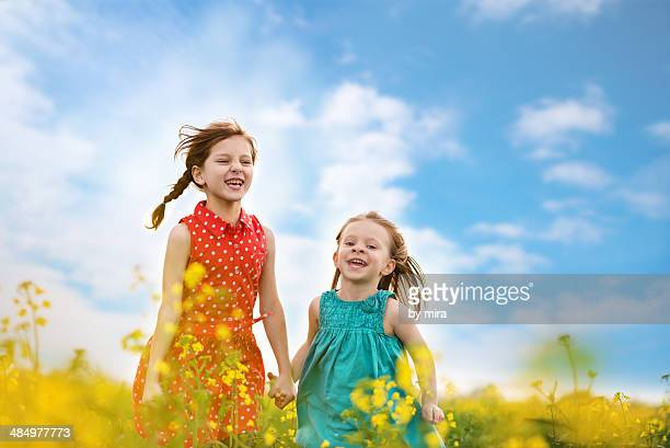 Two girls running in field blossomed