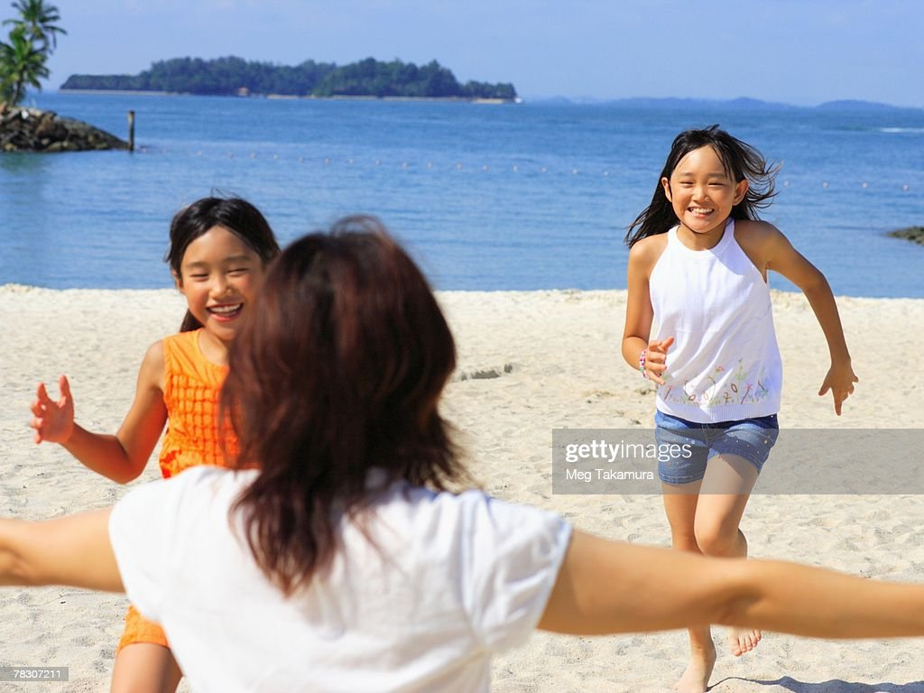Two girls running on the beach towards their mother : Stock Photo