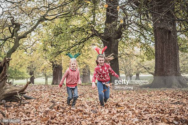 Two girls running through Autumn leaves in forest