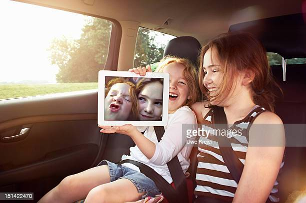Two girls showing photo taken on digital tablet
