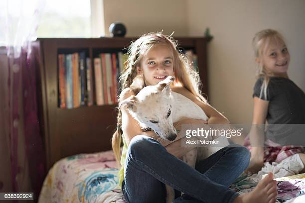 Two girls, sisters, playing with dog in kids room