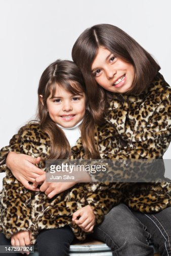 Two girls sisters wearing same leopard coat : Stock Photo