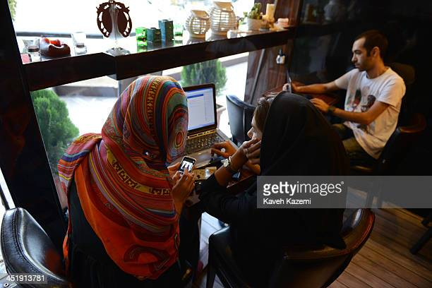 Two girls sit in a north Tehran coffee shop using Facebook and looking on the mobile phone at online fashion clothing in Tehran Iran on October 13...