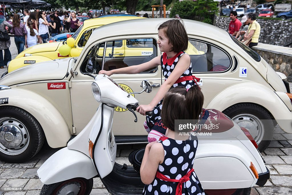 Two girls sit on a a vintage motor scooter displayed during the 11th Old Timers Fest on May 29, 2016 in Prizren. / AFP / ARMEND