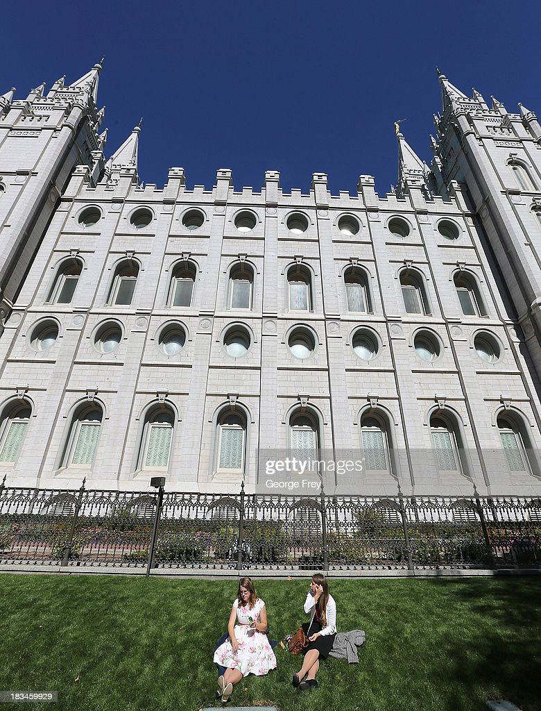 Two girls sit on the grass by the Mormon temple on Temple Square during the 183rd Semi-Annual General Conference of the Church of Jesus Christ of Latter-Day Saints in Salt Lake City, Utah on October 6, 2013.