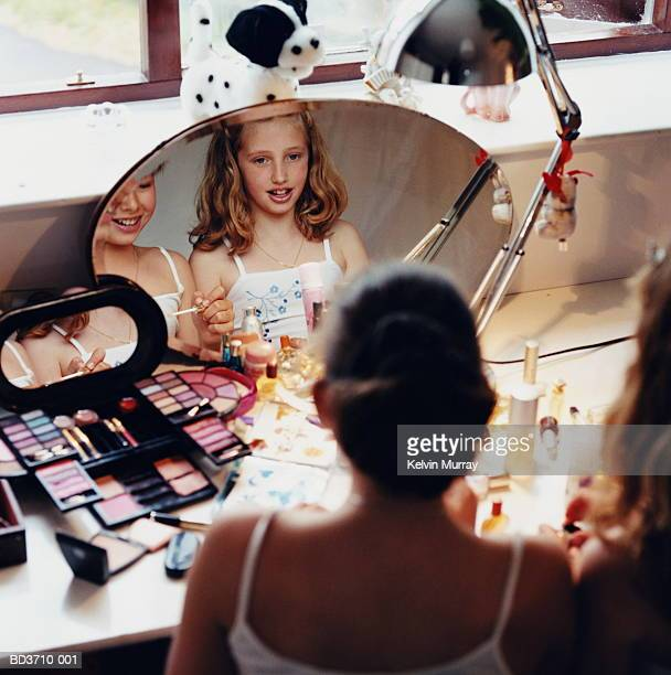 Two girls (10-12) sitting at dressing table, putting on make-up