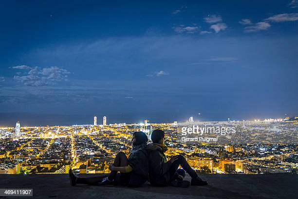 Two girls sitting at night watching Barcelona