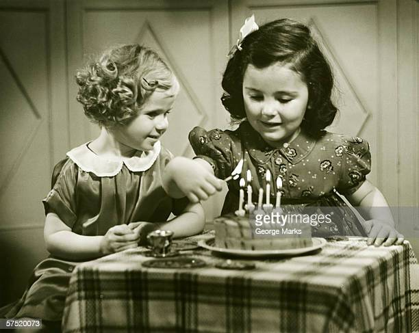Two girls (3-4), (4-5) sitting at small table with birthday cake, (B&W)