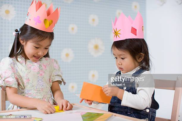 Two girls (2-5) sitting at table, doing origami