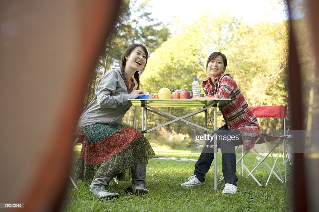 Two girls sitting at table, laughing : Stock Photo
