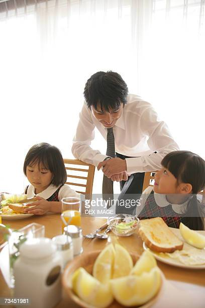 Two girls sitting at the dining table with their father leaning against their chairs
