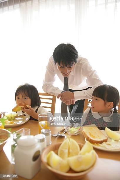 Two girls sitting at the dining table with their father leaning against their chairs behind them