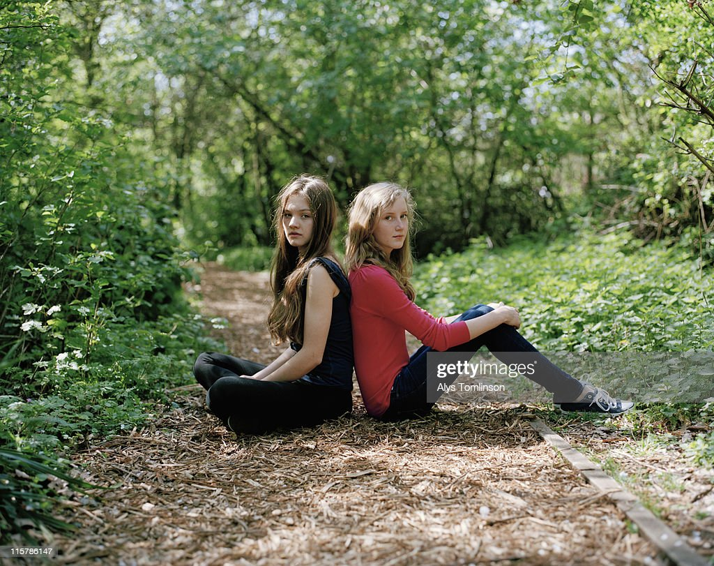 Two Girls Sitting Back to Back in a Forest : Stock Photo