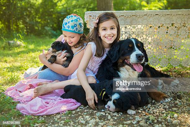 Two girls sitting in garden with a dog and puppies