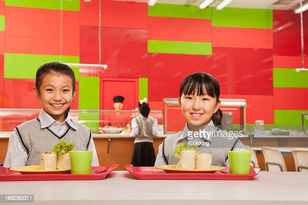 Two girls sitting in school cafeteria