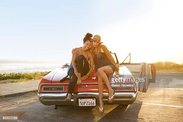 two girls sitting on a car