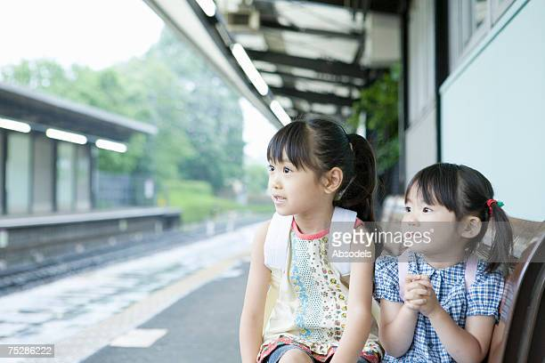 Two girls sitting on a platform bench in a station