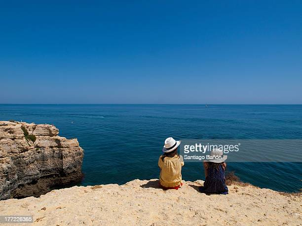 Two girls sitting on a rock looking at the sea