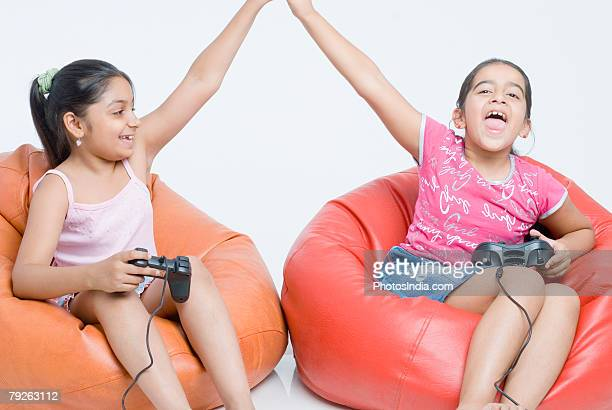 Two girls sitting on bean bags playing video game and giving high-five