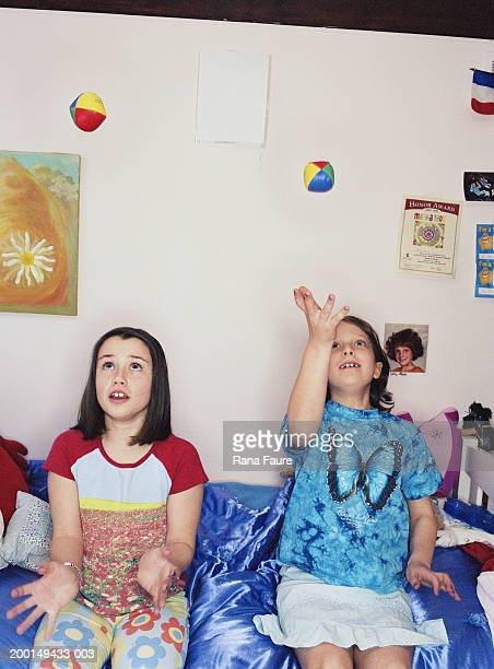 Two girls (7-10) sitting on bed, playing catch