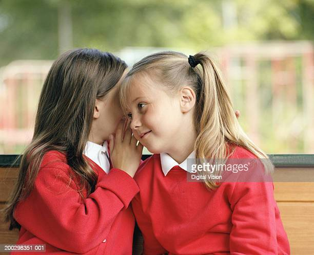 Two girls (6-8) sitting on bench whispering, close-up