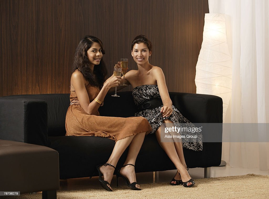 two girls sitting on couch holding champagne toasting. Black Bedroom Furniture Sets. Home Design Ideas