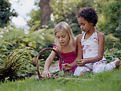 Two girls (6-8) sitting on grass by basket