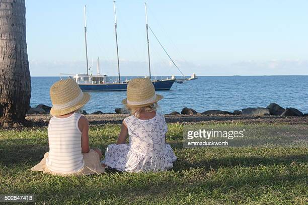 Two girls sitting on grass looking at boat, Port Douglas, Queensland, Australia