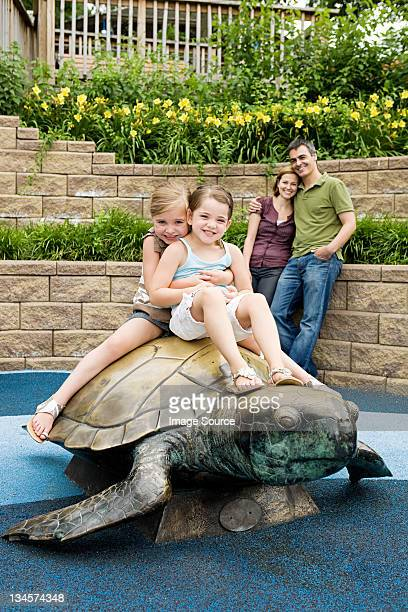 Two girls sitting on top of tortoise statue at the zoo