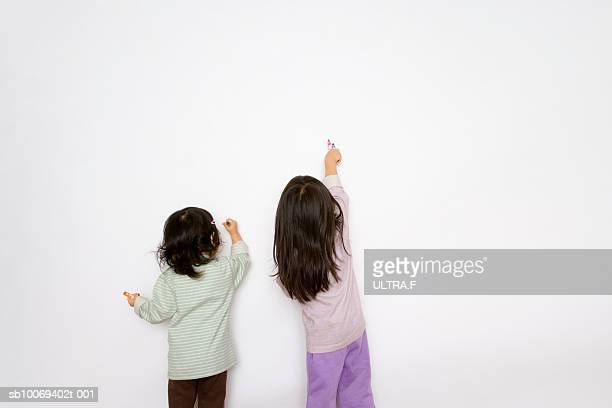 Two girls (2-3) sitting on white wall, rear view