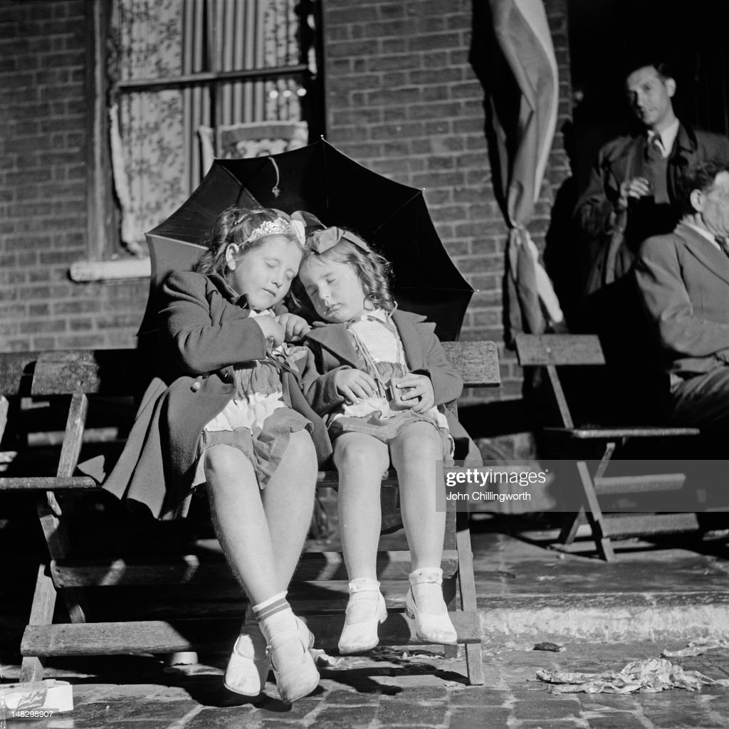 Two girls sleeping under an umbrella at a street party to celebrate the coronation of Queen Elizabeth II, held in Morpeth Street in London's East End, 2nd June 1953. Original publication: Picture Post - 6542 - Cockneys' Own Party - pub. 13th June 1953