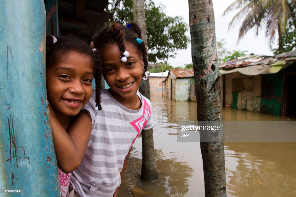 Two girls smile in a flooded area of Santo Domingo, on July 11, 2013 after Tropical Storm Chantal lashed the impoverished Caribbean island of Hispaniola -- shared by Haiti and the Dominican Republic. A firefighter was killed and more than 6500 people were evacuated in the Dominican Republic as Chantal has now weaken into a 'tropical wave'. AFP PHOTO/Erika SANTELICES