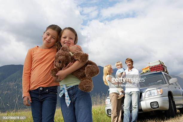 Two girls (6-8 years), smiling, portrait, on road trip with family