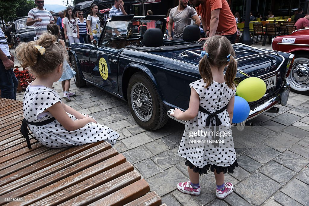Two girls stand in front of vintage cars displayed during the 11th Old Timers Fest on May 29, 2016 in Prizren. / AFP / ARMEND