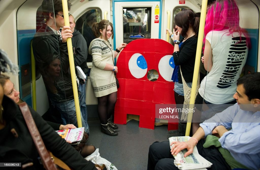 Two girls stand next to a cardboard of a Pac-man ghost on the London underground after leaving the 'MCM London Comic Con' convention at the ExCel center in east London on October 29, 2011. Running over two days, the event will see thousands of comics, sci-fi and gaming enthusiasts coming together to buy, sell and celebrate everything from sporting heroes to Japanese 'Steam Punk' characters.