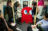 Two girls stand next to a cardboard of a Pacman ghost on the London underground after leaving the 'MCM London Comic Con' convention at the ExCel...