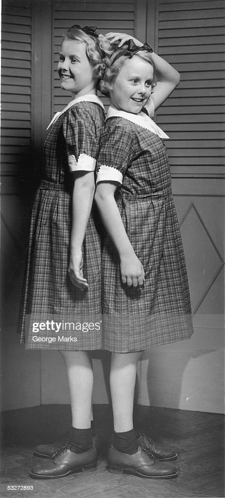 Two girls standing back to back : Stock Photo
