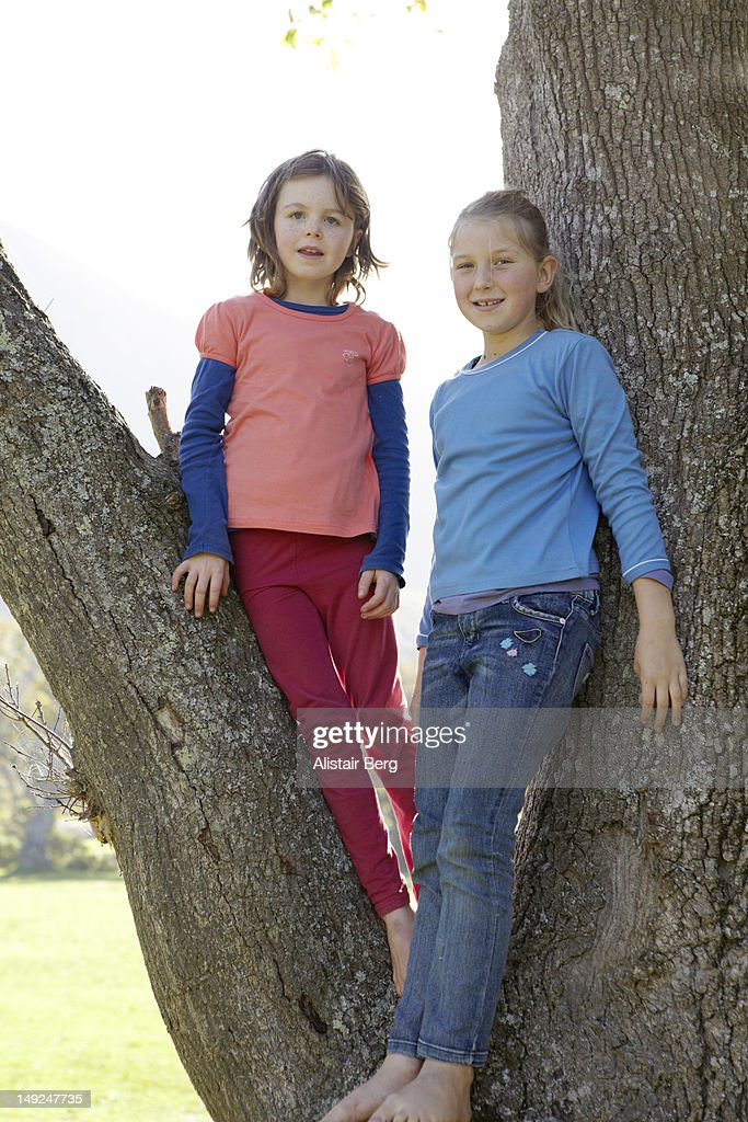 Two girls standing in a tree : Stock Photo