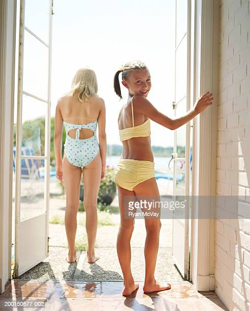 Two girls (9-12) standing in doorway (focus on girl in foreground)