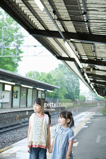 Two girls standing on  a station platform