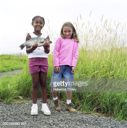 two girls standing side by side one girl holding bass smiling stock foto getty images. Black Bedroom Furniture Sets. Home Design Ideas