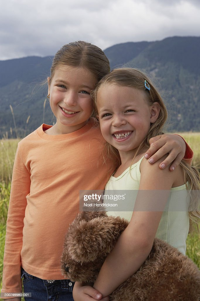 Two girls (6-8 years) standing together outdoors, smiling, portrait : Stock Photo